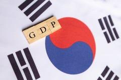 Produtos internos ou GDP bruto de Coreia do Sul em letras de bloco de madeira na bandeira coreana sul foto de stock