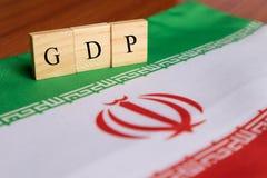 Produtos internos ou GDP bruto de Irã em letras de bloco de madeira na bandeira de Irã fotos de stock royalty free