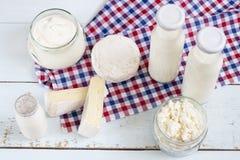 Produtos lácteos Ordenhe na garrafa de vidro, iogurte, queijo do leite ácido, creme de leite no frasco de vidro, camembert, brie  Imagens de Stock
