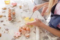 Produtos para cozer As mãos da criança cozinham doces Farinha com massa, ovos, cascas de ovo, e biscoitos na mesa de cozinha fotografia de stock
