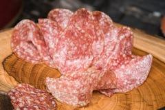 Produtos processados das carnes frias, em uma placa de corte de madeira Fotografia de Stock Royalty Free