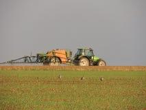 Produtos químicos de pulverização do fazendeiro nos campos imagens de stock royalty free