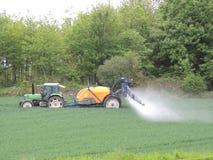 Produtos químicos de pulverização do fazendeiro nos campos foto de stock royalty free