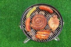 Produtos sortidos da reunião na grade quente do BBQ Opinião de ângulo alto Fotos de Stock Royalty Free