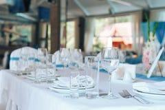 Produtos vidreiros e cutelaria para o jantar abastecido do evento Ajuste festivo da tabela no restaurante foto de stock