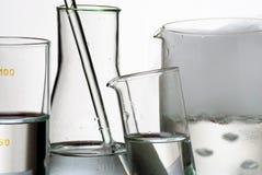 Produtos vidreiros e vapores de laboratório sobre o líquido imagens de stock royalty free