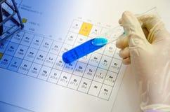 Produtos vidreiros médicos dos tubos de ensaio da posse do cientista da mão na aba periódica foto de stock royalty free