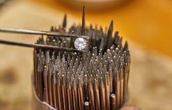 Produzione dei gioielli Il diamante ? tenuto con le pinzette contro i precedenti immagini stock libere da diritti