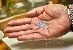 Produzione dei gioielli Il fissatore tiene i diamanti sulla palma prima della riparazione fotografia stock