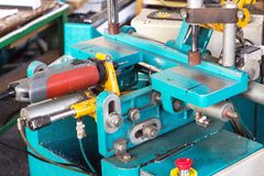 Produzione delle finestre del PVC, una macchina per la fabbricazione dei fori nel profilo di plastica della finestra del PVC, tra immagini stock