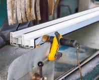 Produzione delle finestre del PVC, una sezione del profilo di plastica sulla macchina della struttura, macchina utensile del PVC fotografia stock libera da diritti
