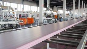 Produzione trattata automatica di materiale da costruzione alla fabbrica con le grandi finestre e la macchina utensile moderna video d archivio