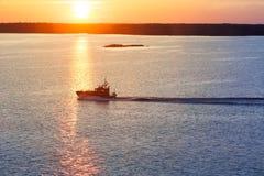 Proefboot die in de kalme wateren bij zonreeks kruisen Stock Fotografie