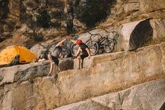 proeffietsers die en hoogte vijf rusten geven aan elkaar dichtbij tent en bergcycli op rotsachtig stock fotografie