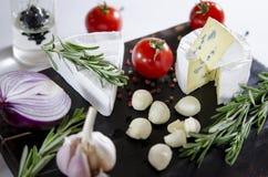 Proevende kaasschotel met tomaten op oude zwarte dask Voedsel voor wijn en romantisch, kaasdelicatessen Horizontaal menuontwerp royalty-vrije stock fotografie