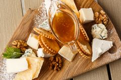 Proevende kaasschotel op een houten plaat Voedsel voor wijn en romantisch, kaasdelicatessen op een houten rustieke lijst bovenkan royalty-vrije stock foto's