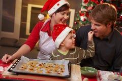 Proevende Kerstmiscake van de papa met familie Stock Afbeeldingen