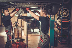 Profecional car mechanic changing motor oil in automobile engin. E at maintenance repair service station in a car workshop stock image