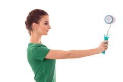 Profeil młody ładny brunetki kobiety budowniczy w mundurze z farba rolownikiem w rękach robi reovations odizolowywającym na bielu Fotografia Stock
