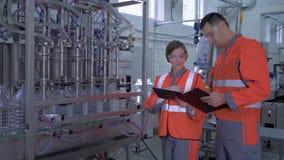 Profesión de la fábrica, mujer joven y trabajadores de la industria del hombre en las batas con la tableta digital a disposición  almacen de metraje de vídeo