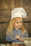 Profesión del cocinero Panadero del muchacho en sombrero del cocinero con el cortador de la galleta Fotografía de archivo
