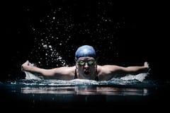 Profesional女子使用蛙泳技术的游泳者游泳在黑暗的背景 免版税库存图片