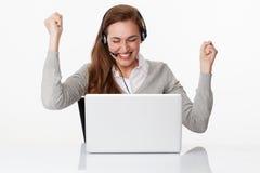 Profesional acertado 20s con las auriculares y el ordenador en la oficina blanca Fotos de archivo