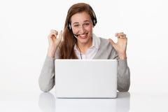 Profesional alegre 20s con las auriculares y el ordenador en la oficina blanca Imagen de archivo libre de regalías
