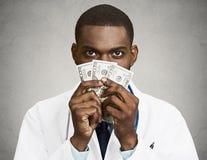 Profesional codicioso de la atención sanitaria, doctor que sostiene el efectivo, dinero Imagenes de archivo