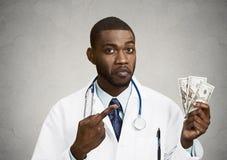 Profesional codicioso de la atención sanitaria, doctor que sostiene el efectivo, dinero Fotografía de archivo libre de regalías