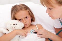 Profesional de salud que controla a la niña enferma Imagen de archivo libre de regalías