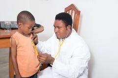 Profesional de salud que examina a un niño Fotos de archivo