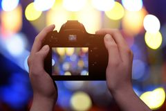 Profesional digital camera in hands. Blue and yellow bokeh in background.  Stock Photos