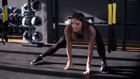 Profesional en deporte Vista delantera de la mujer joven hermosa en la ropa de deportes que hace estirando rato en el piso en una almacen de video