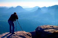 profesional en el acantilado el fotgrafo de la naturaleza toma las fotos con la cmara del