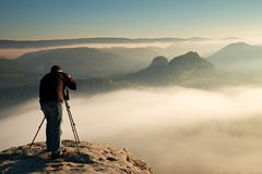 Profesional en el acantilado El fotógrafo de la naturaleza toma las fotos con la cámara del espejo en roca El paisaje soñador de  Fotos de archivo libres de regalías