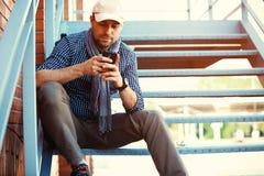 Profesional joven del hombre de negocios en smartphone que camina en calle usando mensaje del SMS del app que manda un SMS en sma fotografía de archivo libre de regalías