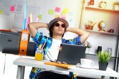 Profesional joven elegante que disfruta de su día de fiesta mientras que trabaja encendido Foto de archivo