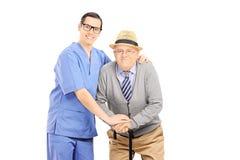 Profesional masculino de la atención sanitaria que ayuda a un viejo hombre con el bastón fotografía de archivo libre de regalías