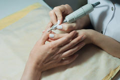 Profesional nail technician sanding nails with machine Stock Photography