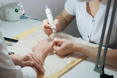 Profesional nail technician sanding nails with machine Stock Images