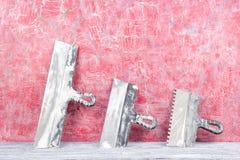 Profesional que repara los instrumentos para el sistema de adornamiento y constructivo de la renovación, pared en el fondo Enyesa Foto de archivo libre de regalías