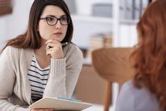 Profesional-Ratgeber mit Notizblock und Stift während der Werkstattsitzungs-Formfrauen stockfotografie