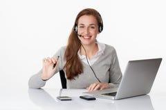 Profesional sonriente 20s con las auriculares y el ordenador en la oficina blanca foto de archivo