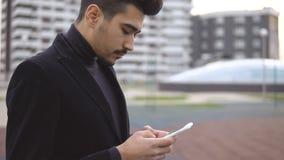Profesional urbano joven del hombre de negocios en traje negro que camina en calle usando mensaje del SMS del app que manda un SM imágenes de archivo libres de regalías