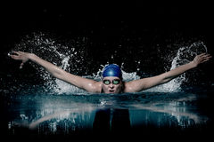 Profesional woman swimmer swim using breaststroke technique on the dark background Stock Photo