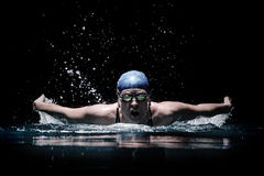 Profesional woman swimmer swim using breaststroke technique on the dark background Royalty Free Stock Images