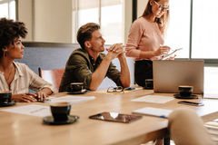 Profesionales corporativos que se sientan alrededor de la tabla durante la reunión fotografía de archivo libre de regalías