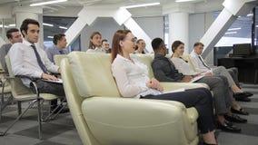 Profesionales jovenes en la reunión semanal en compañía grande dentro metrajes
