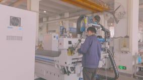 Profesionales jovenes que trabajan en el montaje de la máquina moderna del CNC metrajes